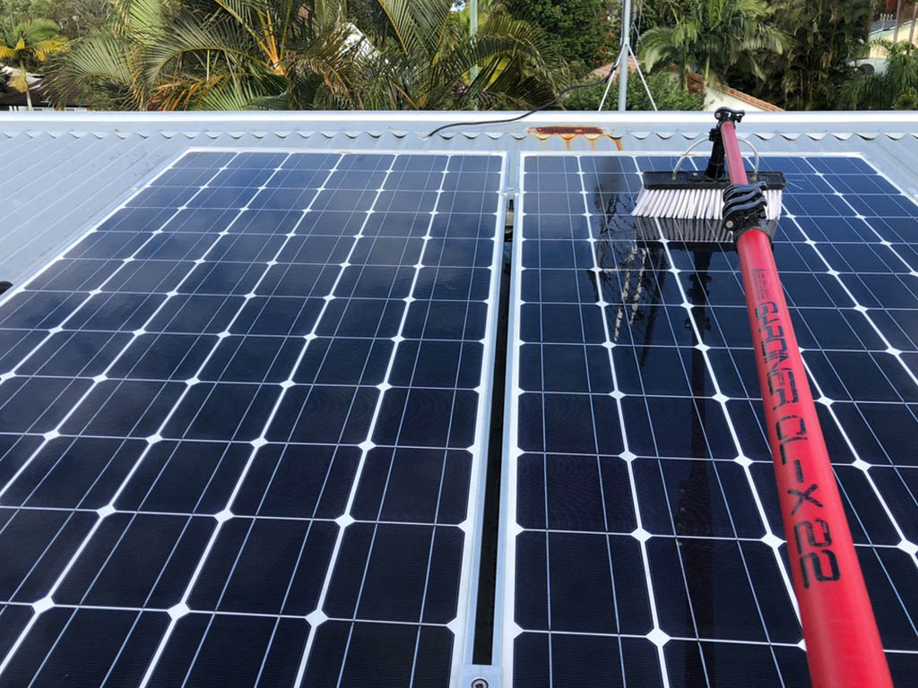 Cleaning a solar panel with a brush and water pump device