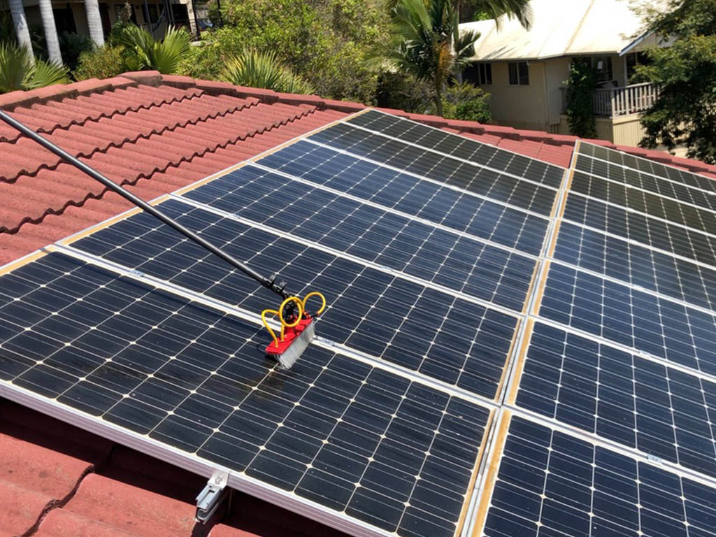 Solar panel cleaned using a brush pole rigged with water pump
