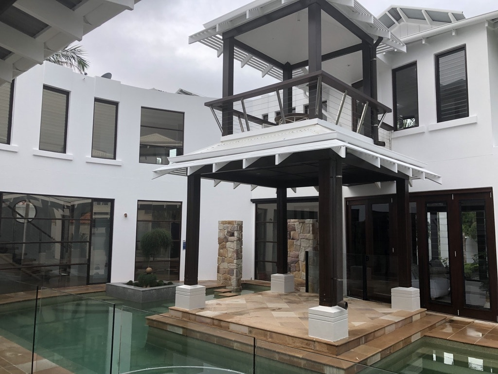 Patio surrounded by pool -- luxurious white house with clean windows